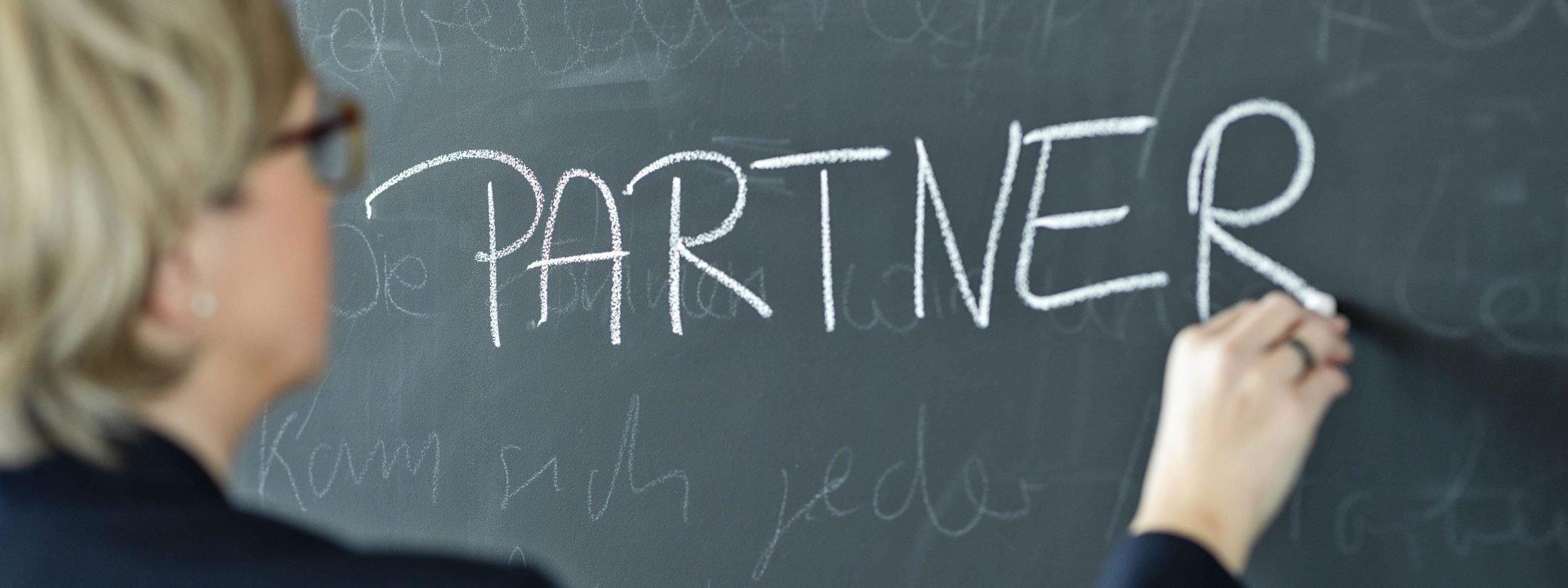"""""""Partner"""" geschrieben auf Kreidetafelwand"""