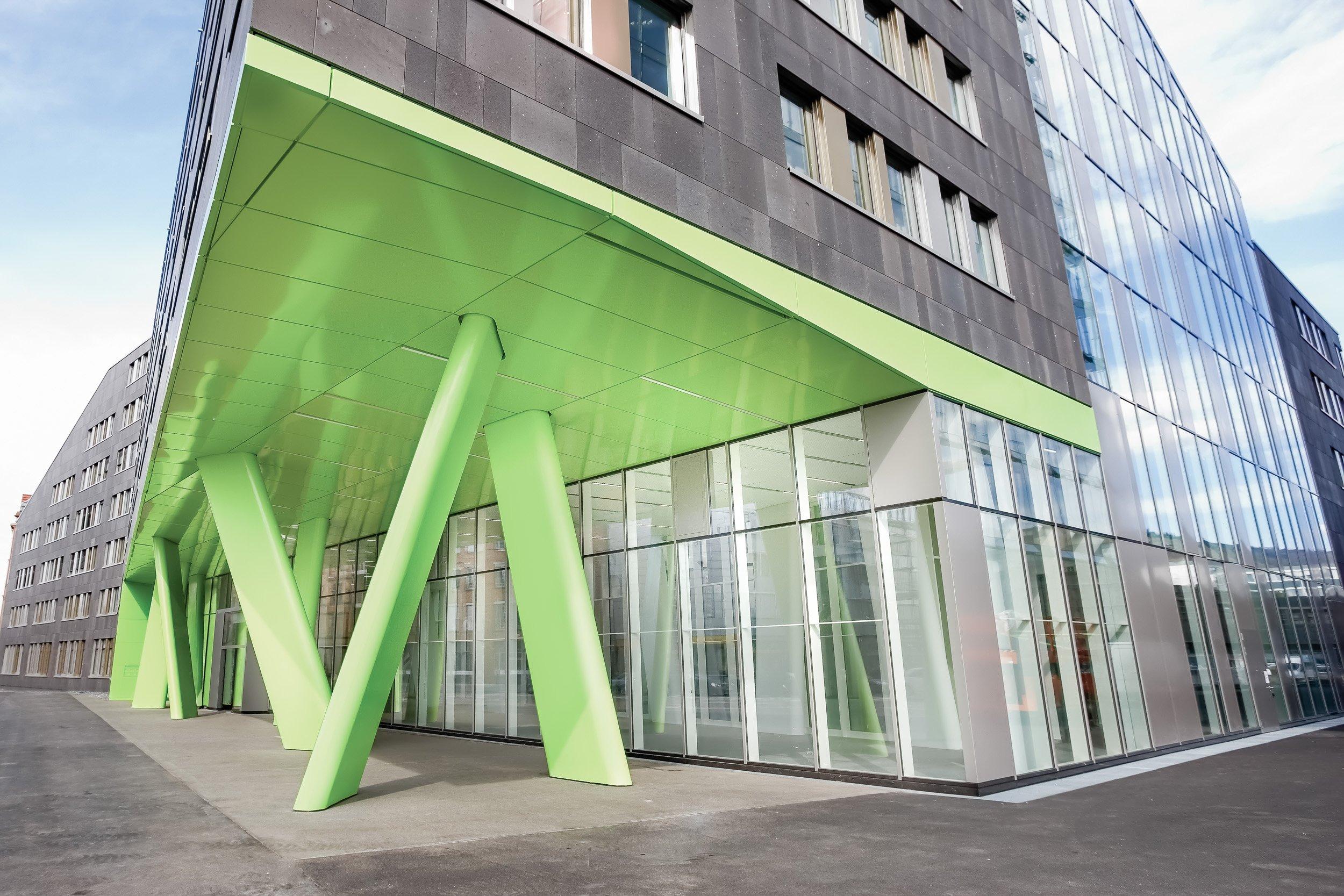 X-House Heidelberg - Außenansicht Eingangsbereich mit grünen Stehlen